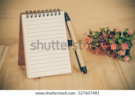 note book  and pen on wood table with vintage tone