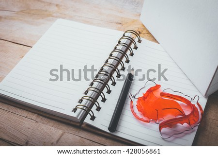 note book and pencil with retainer on wooden table,vintage filter