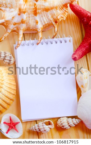 note book and sea shells - stock photo