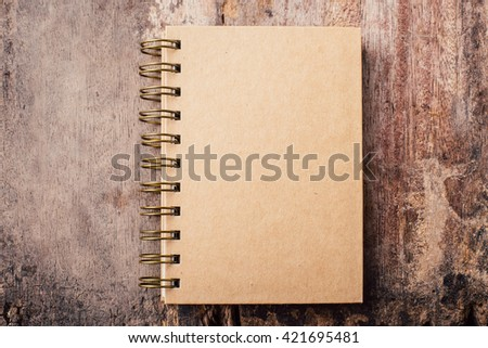 note book on old wooden background - stock photo