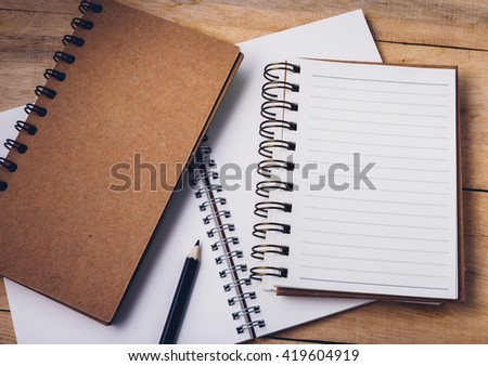 note book on wooden background