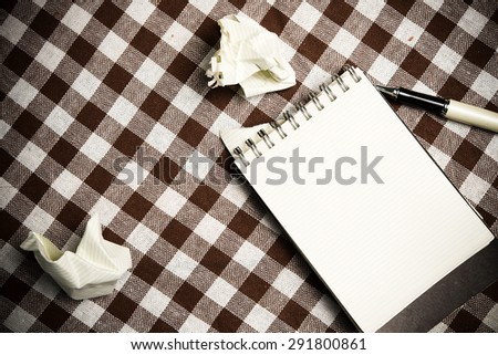 note book paper on old wooden background. - stock photo