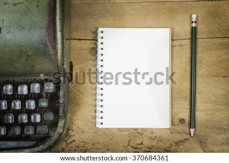 Note book paper on wooden,Blank note book ,Laptop and  Typewriter,roses with hand working on old wooden table, valentine,business concept,Vintage tone,selective focus.can be used for display. - stock photo