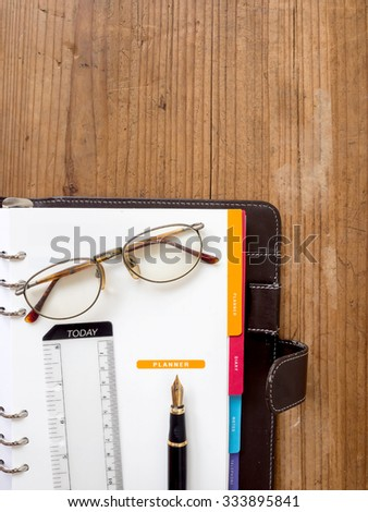 note book paper with pen and glassas on planner page - stock photo