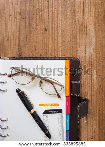 note book paper with pen and glasses on planner page - stock photo