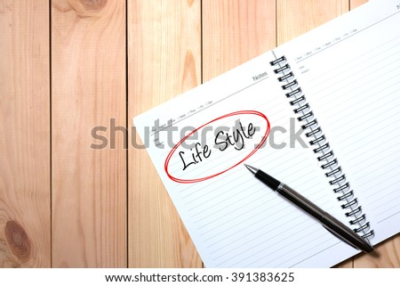 Note Book with Black Pen. Writing LIFE STYLE  in Red Circle with wooden pallet background.