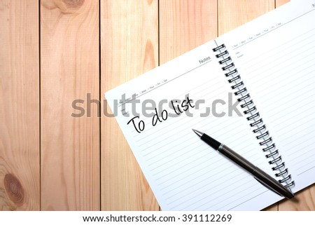 Note Book with Black Pen. Writing To Do List with Wooden Pallet Background. - stock photo