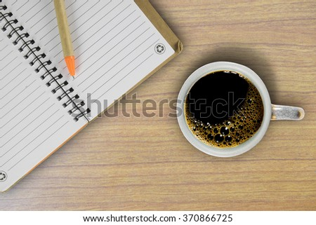 Note book with coffee cup on wood table. Top view.