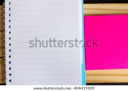 Note book with pink notepaper and pen on wood table background - stock photo
