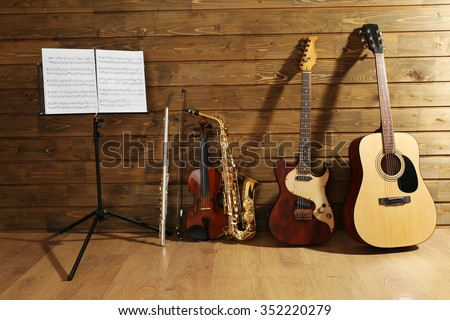Note holder against musical instruments on wooden background - stock photo