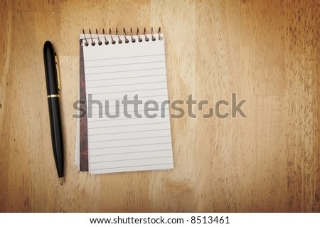 Note Pad and Pen on Wood Background - stock photo