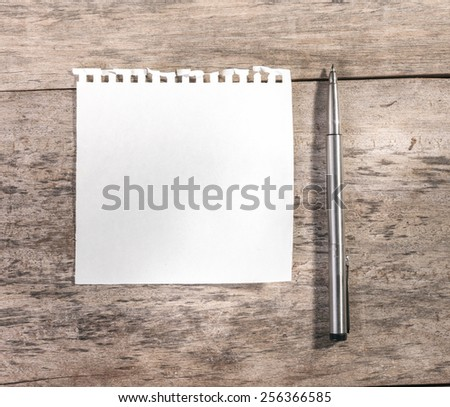 Note pad or memo pad on an old grungy wooden board or surface. - stock photo