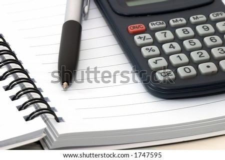 Note pad with pen and calculator on it.Closeup. - stock photo