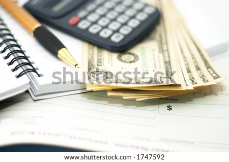 Note pad with pen, calculator and cheque book and cash. Check book. Shallow depth of field - stock photo