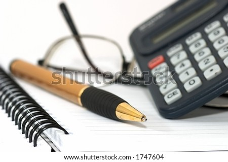 Note pad with pen, calculator, and glasses. glasss on table depicts tiredness - stock photo