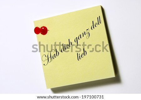 """note pad with the German words """"Hab dich ganz doll lieb"""", translation: love you lots - stock photo"""