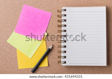 note paper and note book on cork board background - stock photo