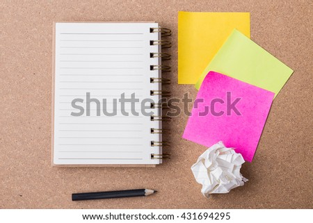 note paper and note book with crumpled paper on cork board background - stock photo