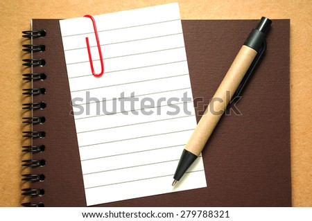 Note paper clip on notebook with pen on brown cardboard background - stock photo