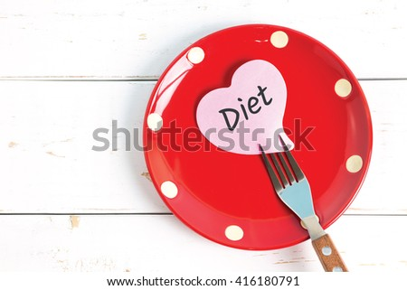 Note paper with message attached to fork, on plate, on wooden background. Healthcare diet concept. - stock photo