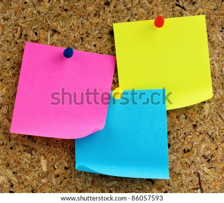 Note paper with push pins on noticeboard - stock photo