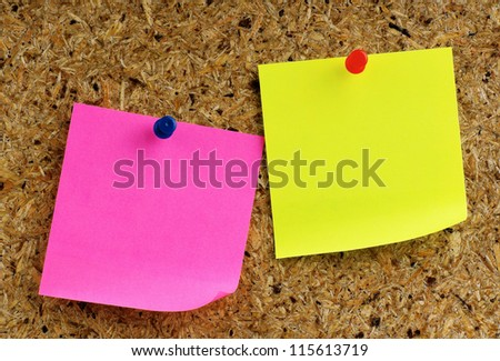 Note paper with push pins on the noticeboard - stock photo