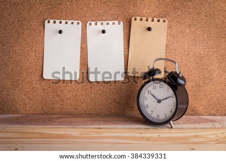 note papers on cork board with alarm clock on wooden floor - stock photo
