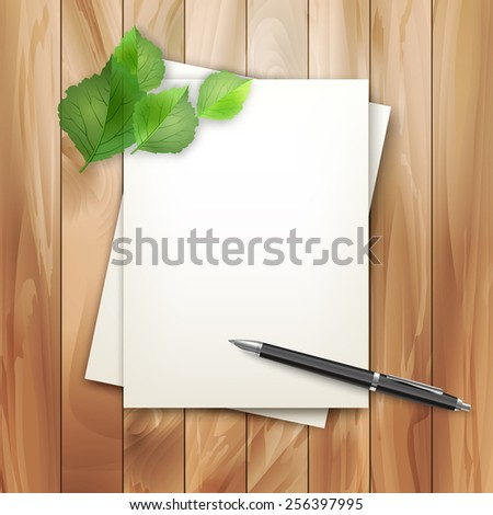 Note sheets of paper with green leaves and pen on vintage wooden planked background - stock photo