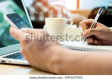 Note taking while use smartphone and laptop computer - stock photo