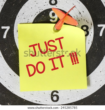 Note with just do it. Darts arrow with yellow sticky note with just do it pined on target center - stock photo