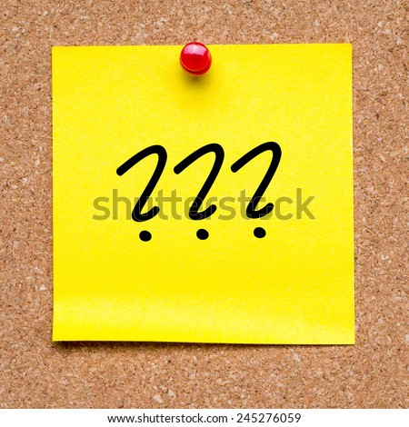 Note with question marks. Blank yellow sticky note with question marks pined on a cork bulletin board. - stock photo