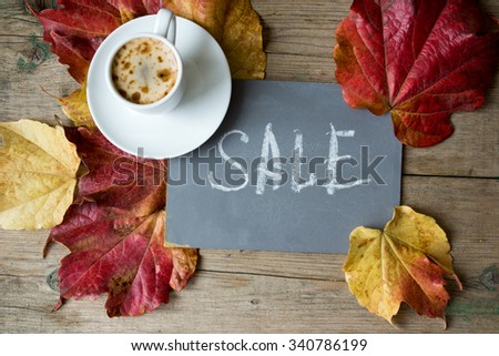 Note with Sale word on the chalkboard, cup of coffee and bright colors ivy plant leaves on wooden background