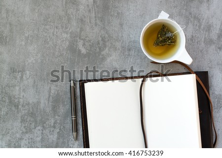 Notebook and a cup of tea on concrete table - stock photo