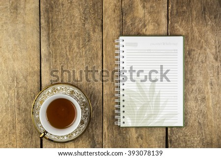 Notebook and a glass of tea or coffee on a wooden table.