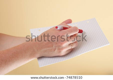 Notebook and a red pen in the hands of women