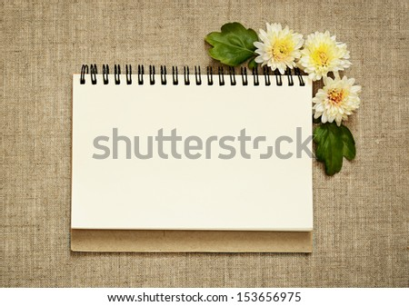Notebook and asters in a corner on gray canvas background - stock photo