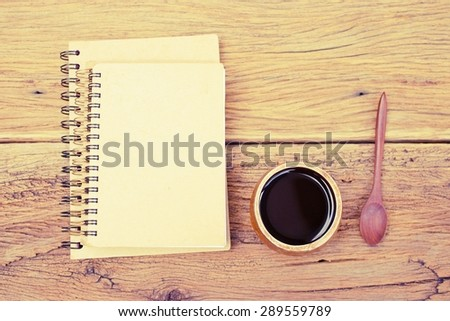 Notebook and  black coffee in wooden cup on wooden table