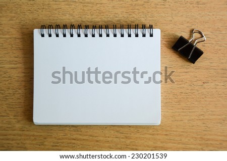 notebook and black paper clip on wood desk - stock photo
