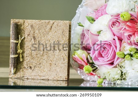 Notebook and bouquet on the glass table - stock photo