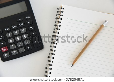Notebook and calculator on a white table .