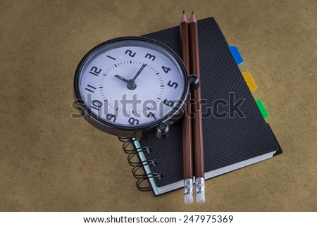 Notebook and clock,pencils