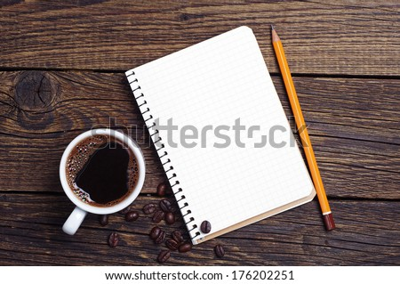 Notebook and coffee on wooden background - stock photo