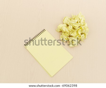 Notebook and crumpled paper on wooden table - stock photo