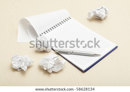 Notebook and crumpled paper wad with pen - stock photo