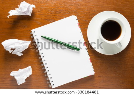 notebook and crumpled sheets of paper on top of view