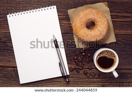 Notebook and cup of hot coffee with donut on old wooden table, top view - stock photo