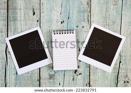 Notebook and instant photo frames on old wooden table - stock photo