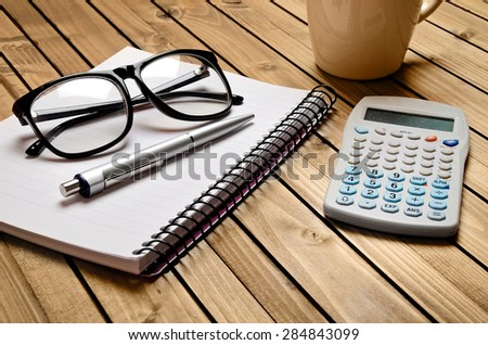 Notebook and office supply on table - stock photo