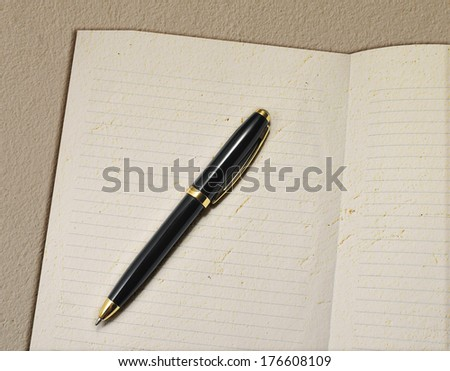 Notebook and pen on grunge background - stock photo