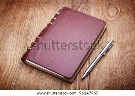 notebook and pen on wood background - stock photo